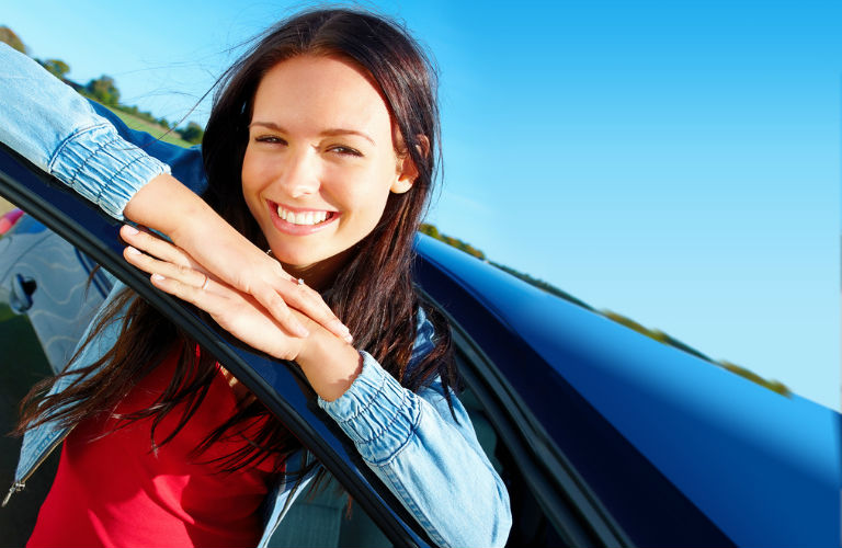happy woman standing outside of car leaning on open car door