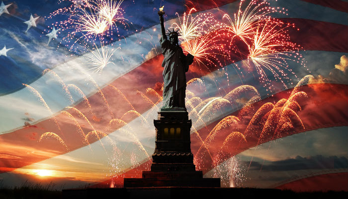 The Statue of Liberty with American flag and fireworks in background