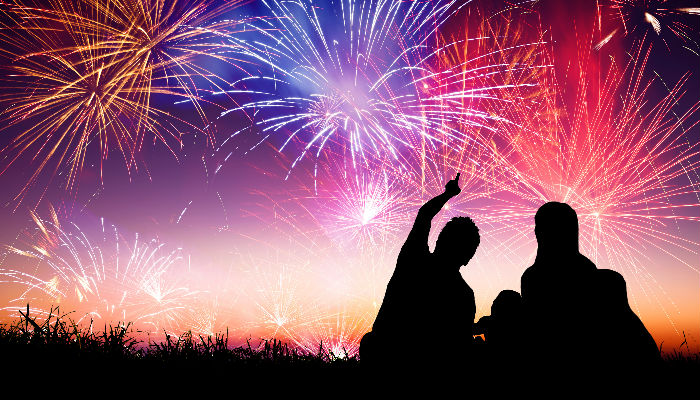 silhouettes of people watching fireworks