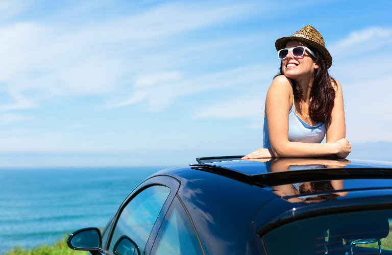 woman wearing sunglasses and hat leaning out of sunroof with ocean behind her
