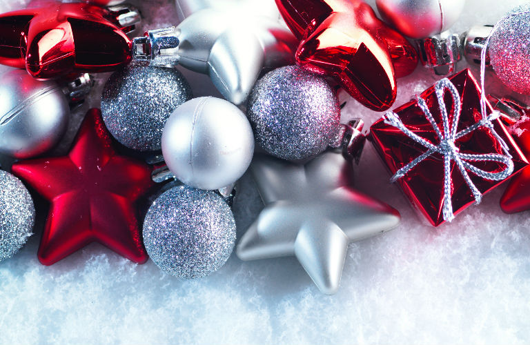 red, white, and silver Christmas ornaments and decorations on a fake snow background