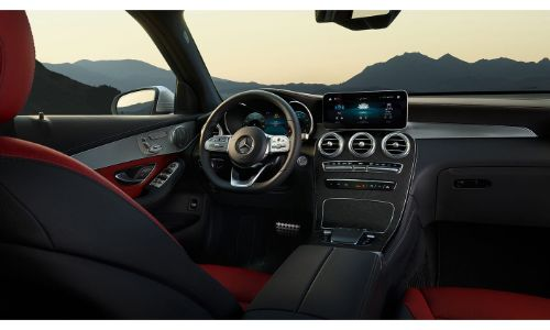 2020 Mercedes-Benz GLC SUV interior shot from between seats showing red and black trim seats with dashboard and steering wheel