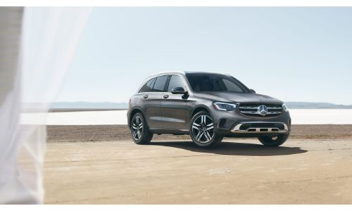 2020 Mercedes-Benz GLC SUV parked on sand in front of water seen through window with curtain on right side