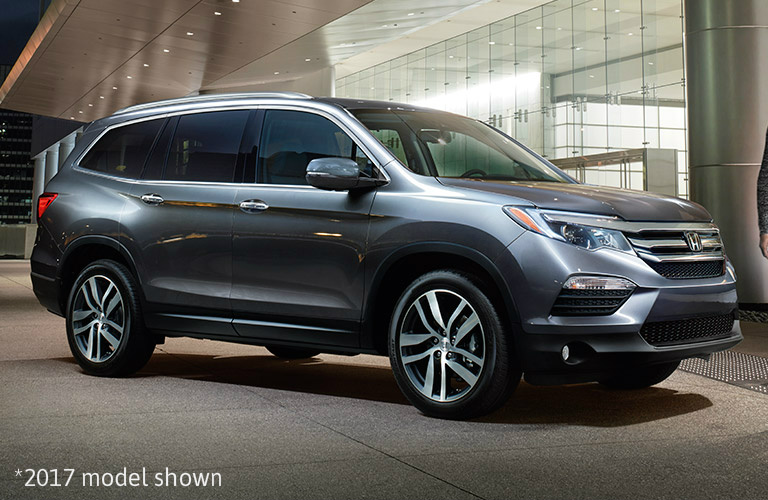 silver 2017 Honda Pilot next to building with text saying *2017 model shownn