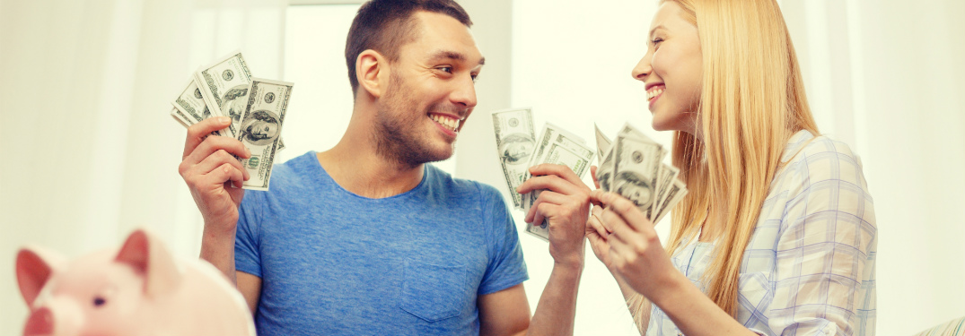 couple holding $100 bills smiling at each other