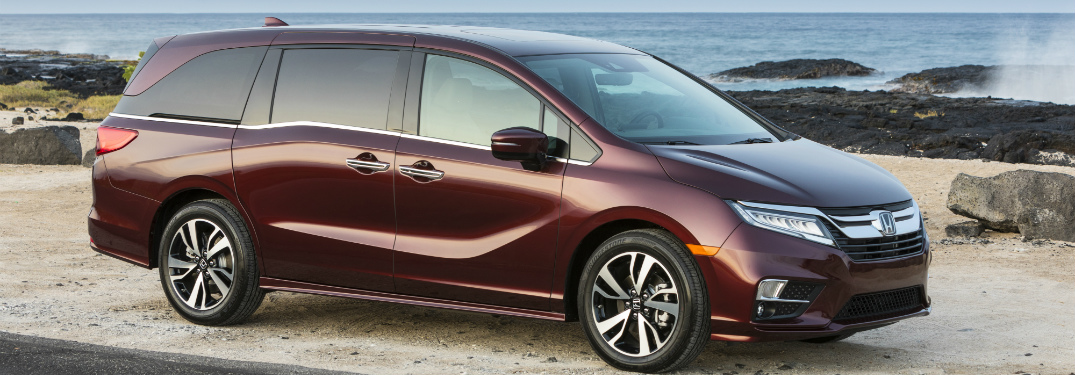 dark red Honda Odyssey minivan parked next to the beach and ocean