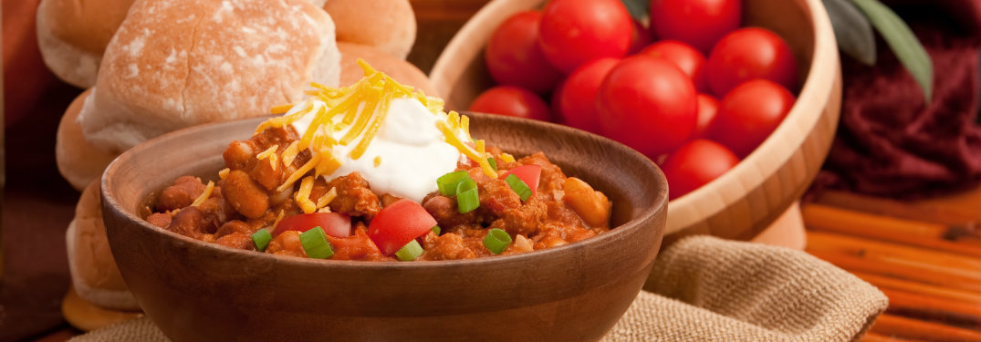 bowl of chili and sour cream, tomatoes in background