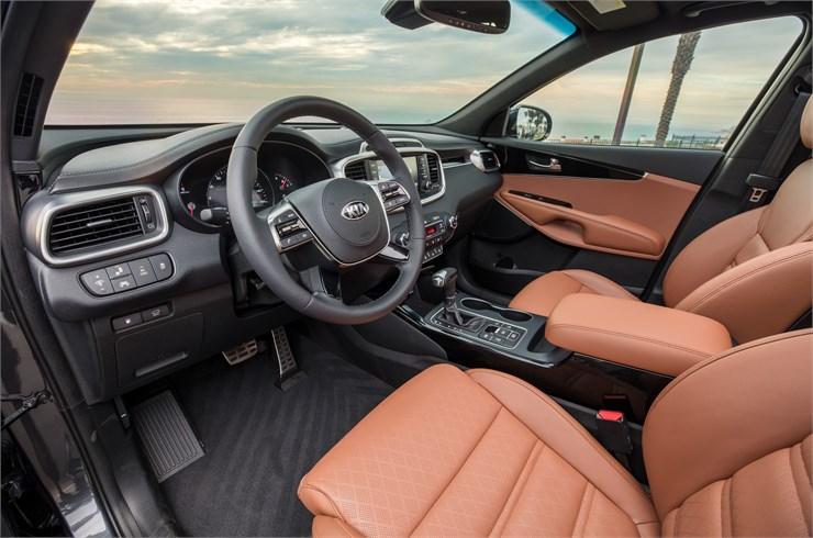 view of tan seats and steering wheel inside the Kia Sorento