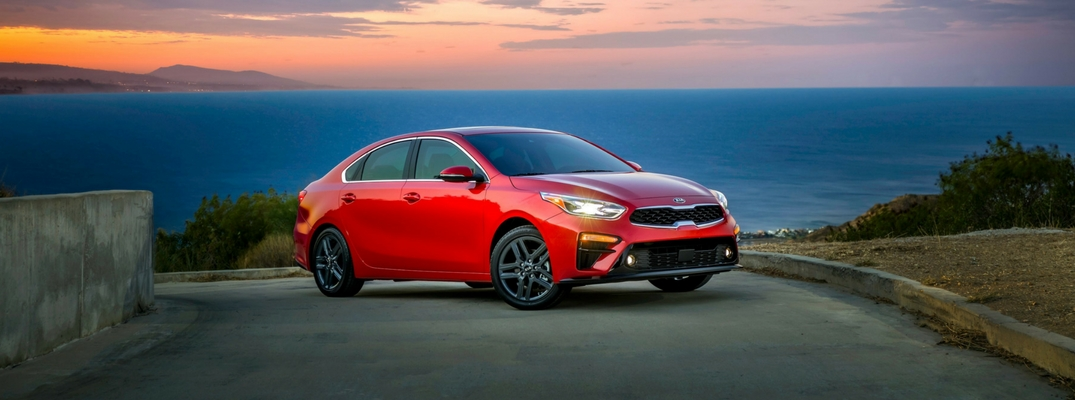 2019 Kia Forte Front View of Red Exterior with Sunset and Ocean Backdrop