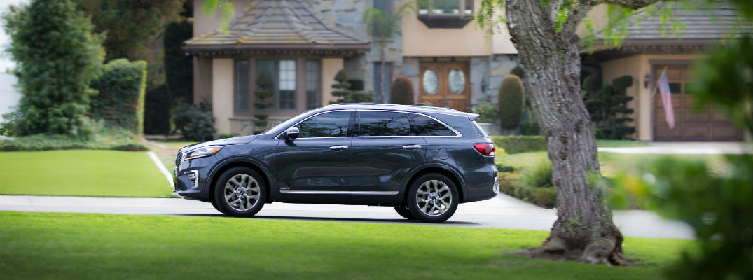 A left profile photo of the 2019 Kia Sorento parked in front of a house.