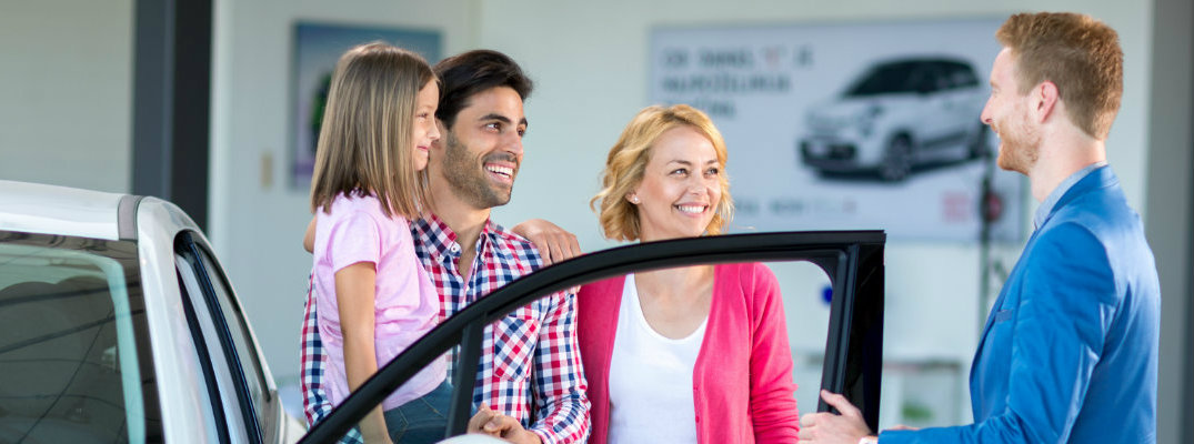 Family with a salesman at a car dealership