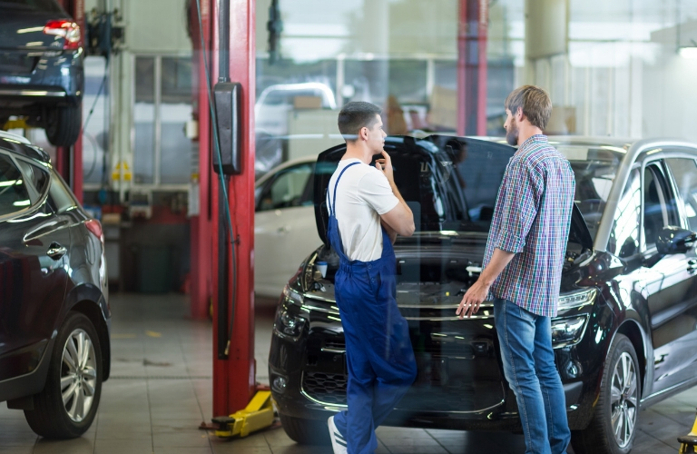 Mechanic Speaking with Client by Vehicle