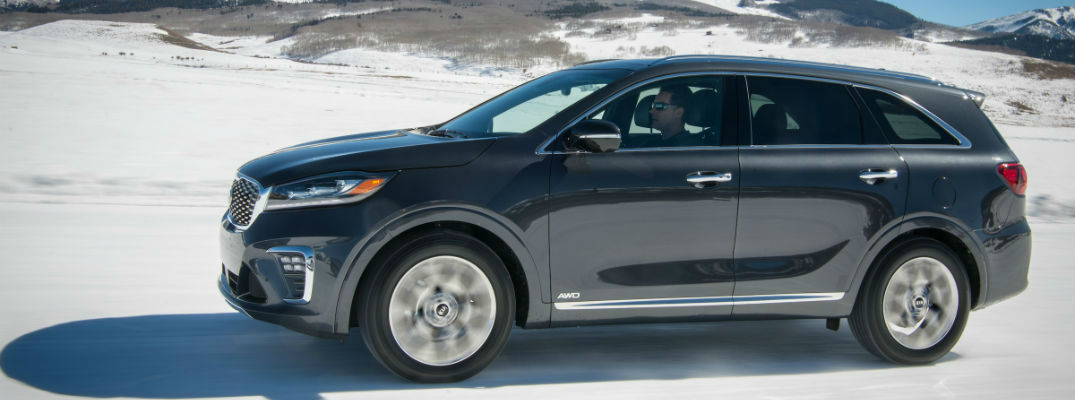 A left profile photo of the 2020 Kia Sorento driving in the snow.