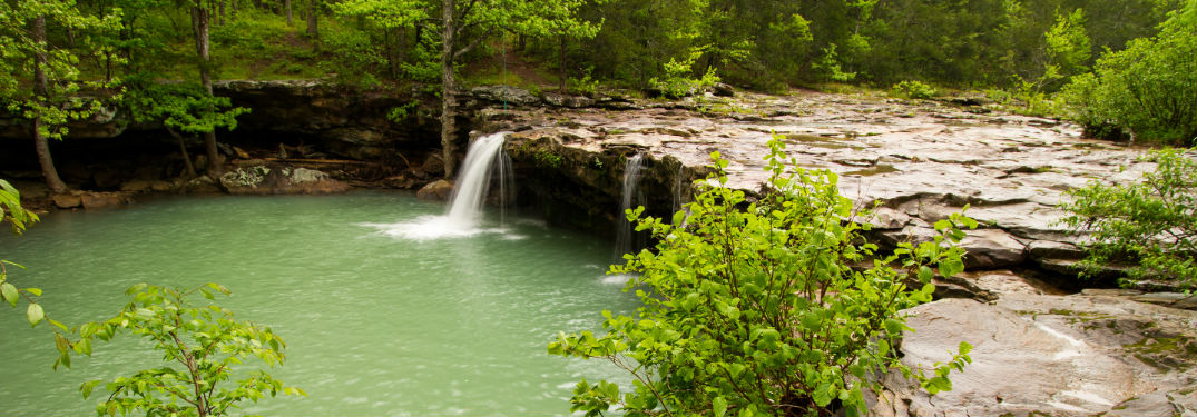 Waterfall in forest with rock path
