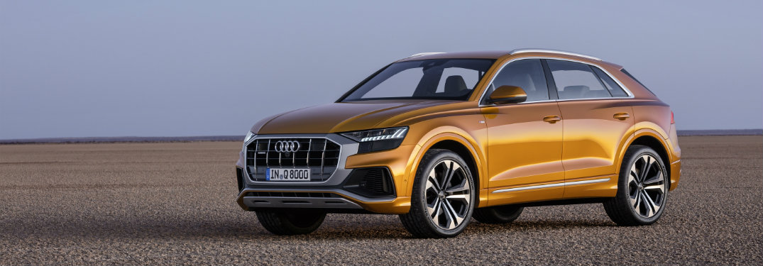 front-side-view-of-orange-2019-Audi-Q8-parked-in-a-flat-open-area