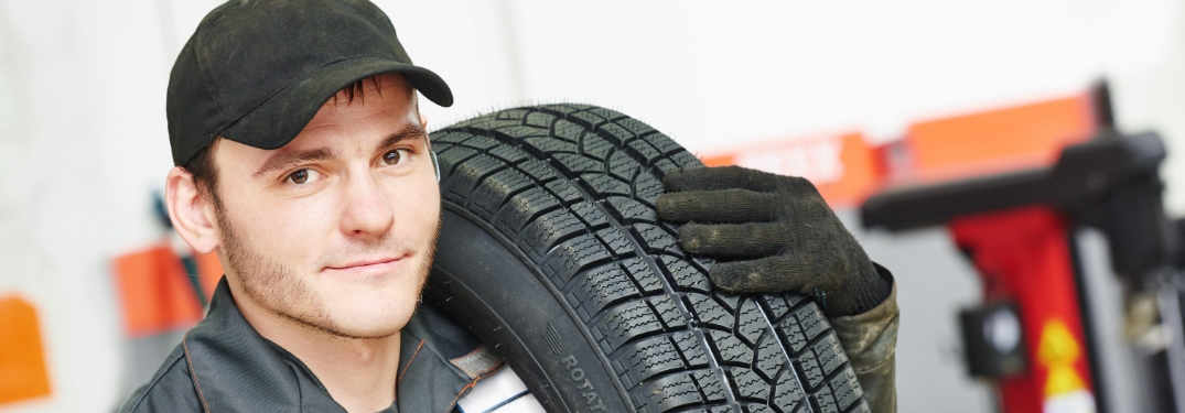 Mechanic carrying a tire in service shop