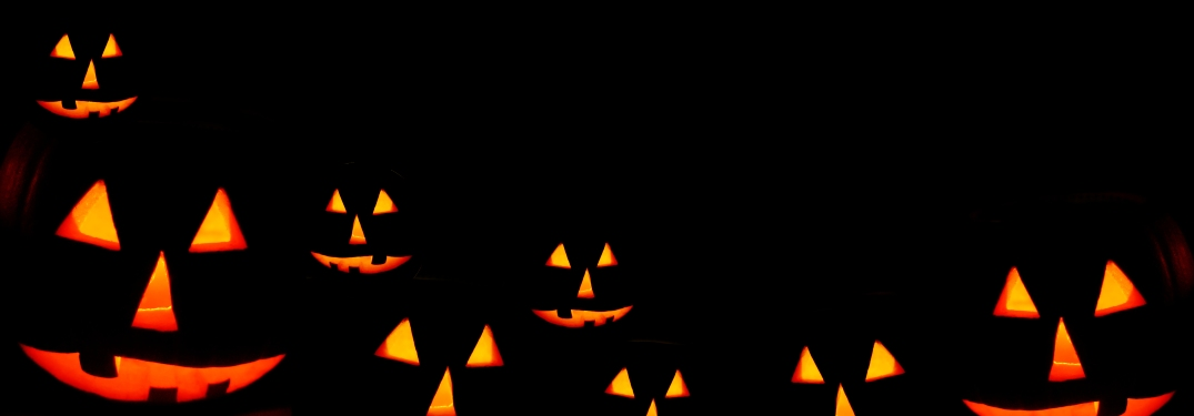 A row of glowing, carved pumpkins in the dark