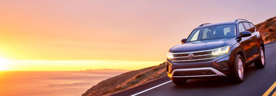 2021 Volkswagen Atlas driving down a curving oceanside road at sunset