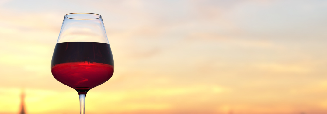 Close-up on a wine glass with a sunset behind it