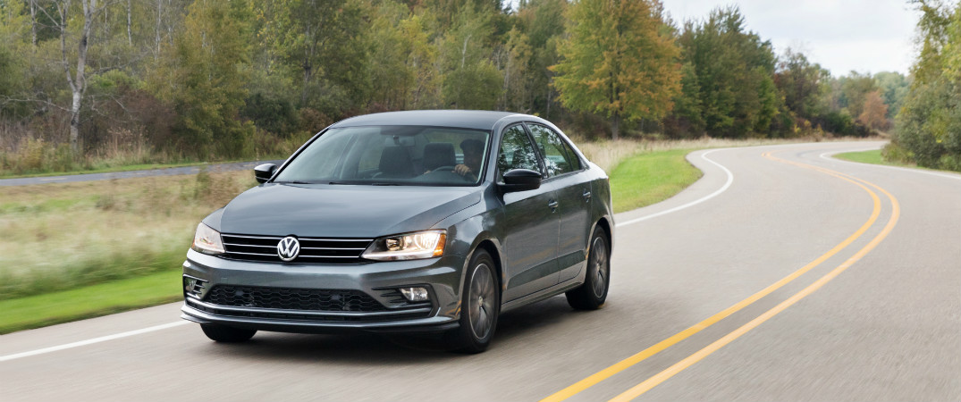 gray 2018 vw jetta driving on scenic road