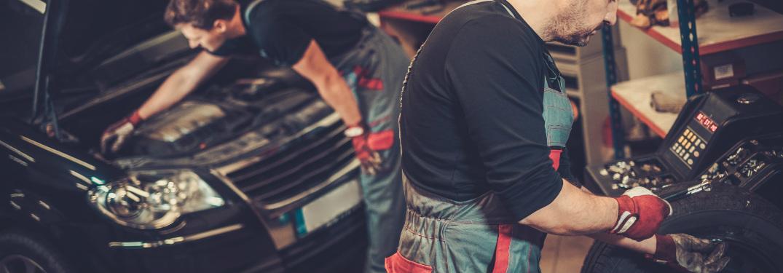 Car mechanics working in an auto body shop