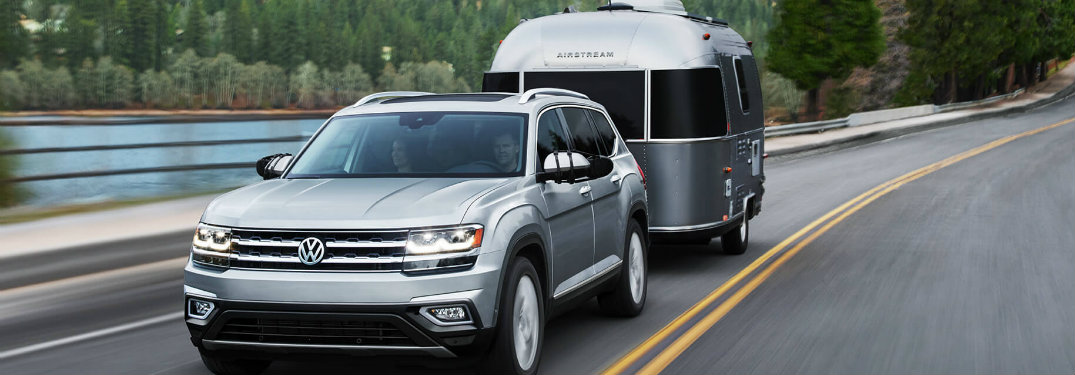 Silver 2018 VW Atlas towing a small camper