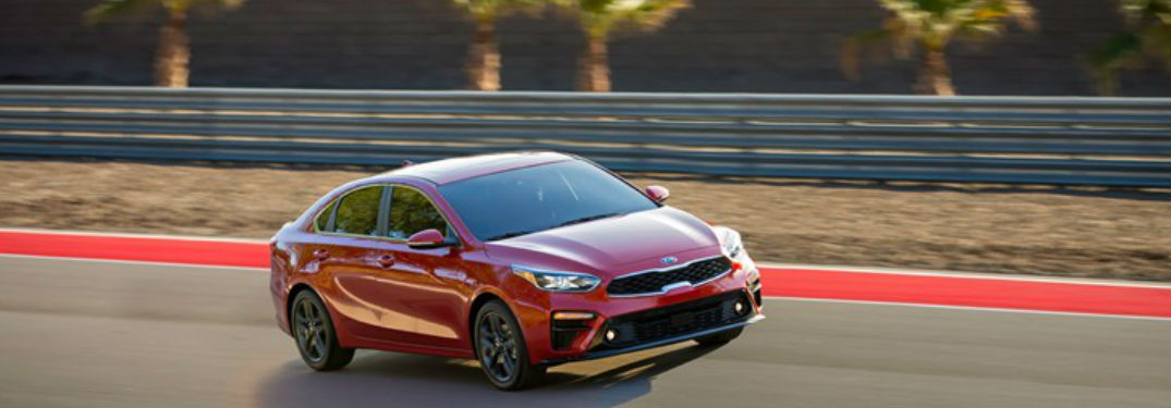 Red 2019 Kia Forte driving down a road