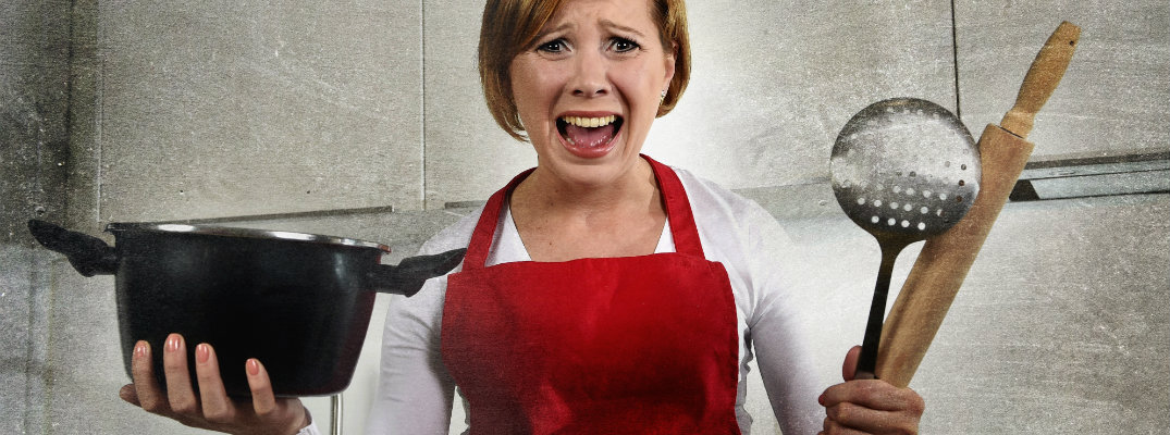 Stressed out woman wearing a red apron in the kitchen