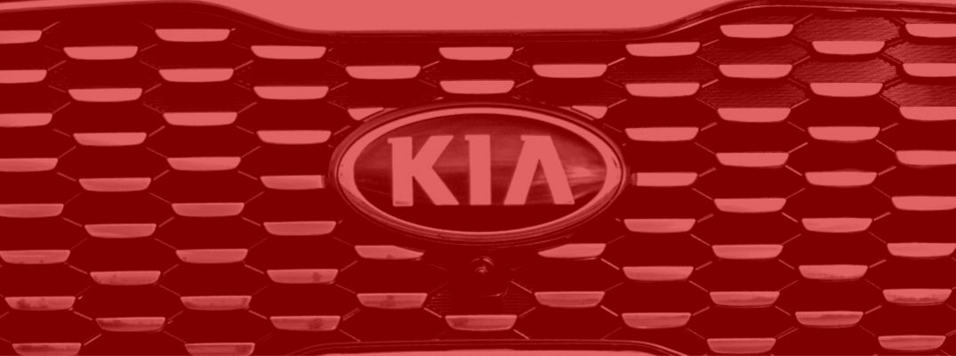Red tinted image of a Kia vehicle's front grille and badge