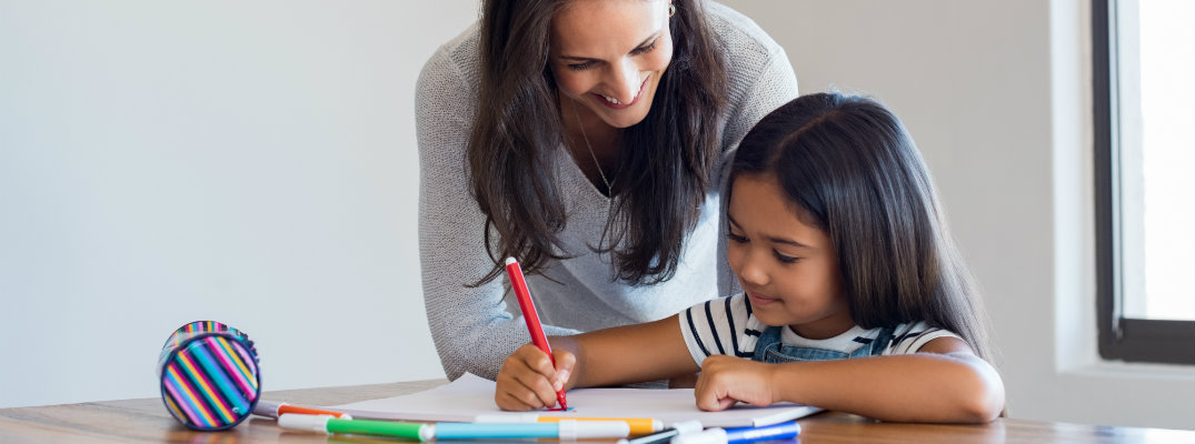 Mother and daughter coloring a picture at home