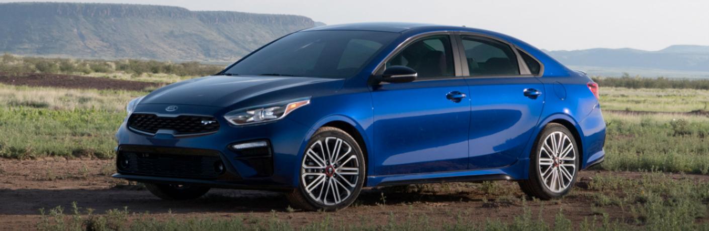 Blue 2020 Kia Forte parked on a grassy field
