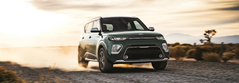 Green 2020 Kia Soul driving on a gravel road