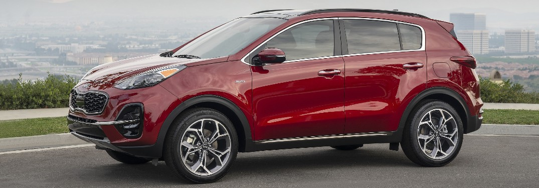 Red 2021 Kia Sportage with a city skyline in the background