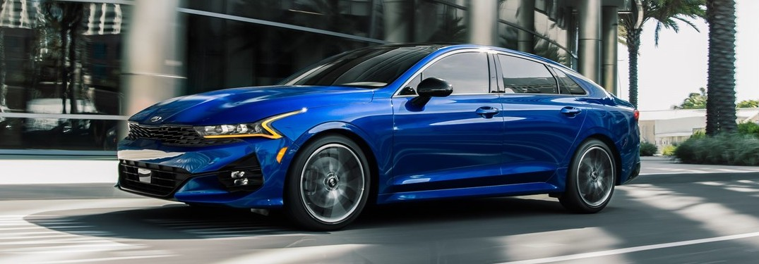 Blue 2021 Kia K5 driving by a building with large glass windows