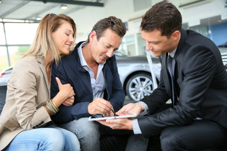 couple signing for a vehicle purchase with a car salesman