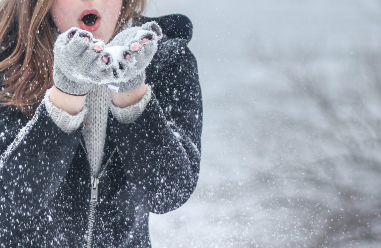girl with cupped hands blowing on snow