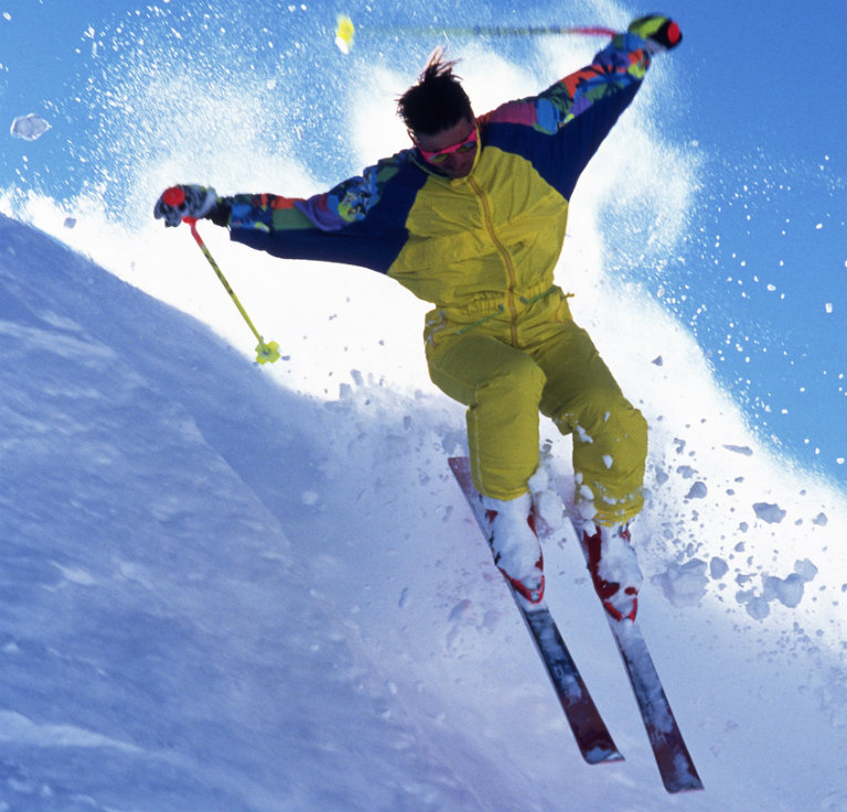 guy in a yellow snow suit skiing down hill athletically