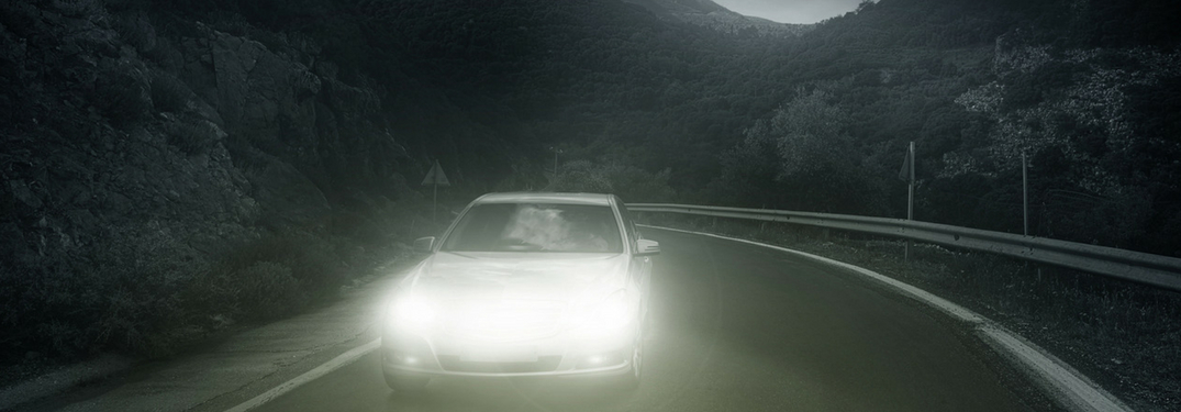 car with headlights on driving at night
