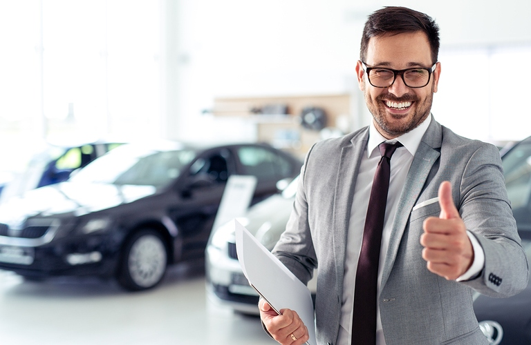 Happy car salesman in front of vehicles
