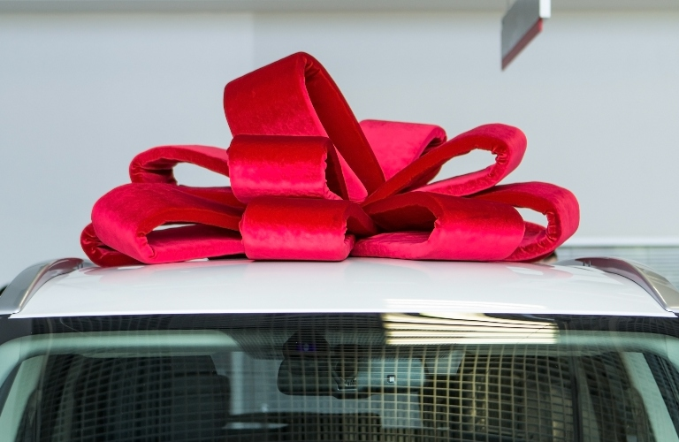 Big red bow on top of a vehicle