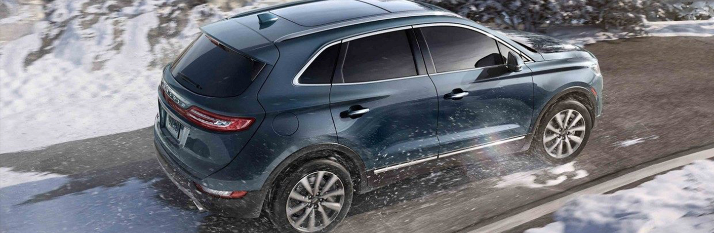 blue 2019 lincoln mkc on snowy wet road