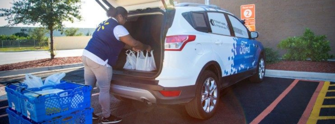 Walmart employee loads groceries into trunk of Ford delivery vehicle