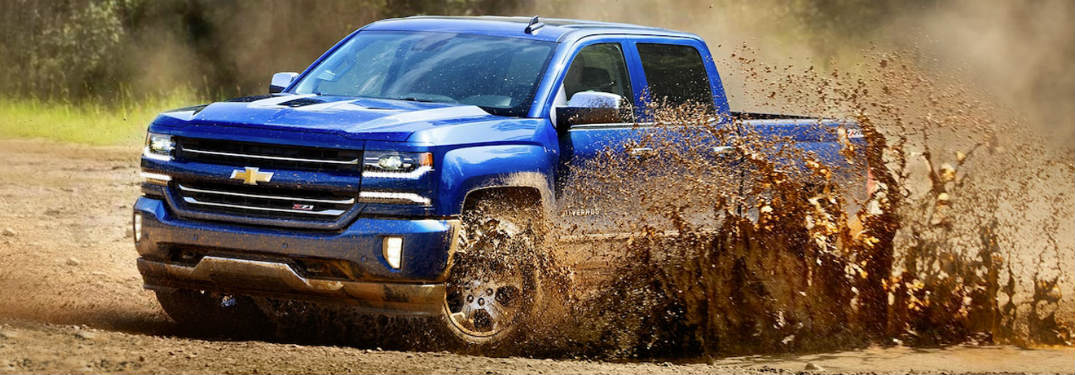 2018 Chevrolet Silverado blue driving through mud