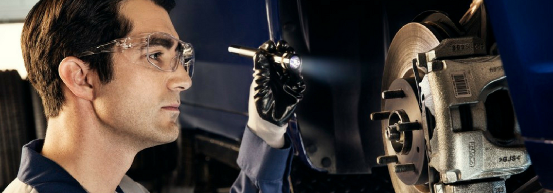 Technician inspects brakes with flashlight