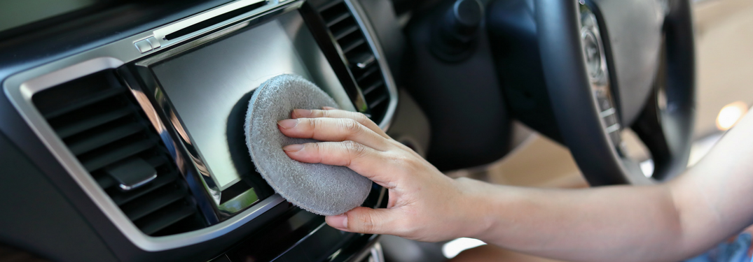 person cleans infotainment screen with microfiber cloth
