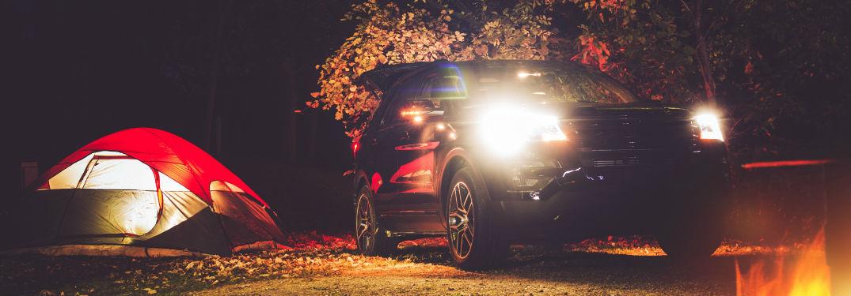 tent, SUV, and campfire at night