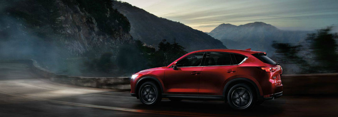 Mazda CX-5 driving on a road with mountains in the background