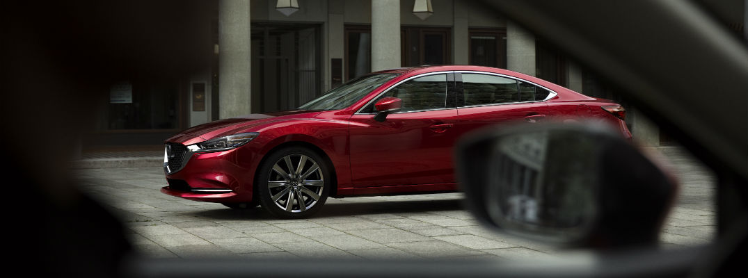 A left profile photo of the 2019 Mazda6 parked on the street.