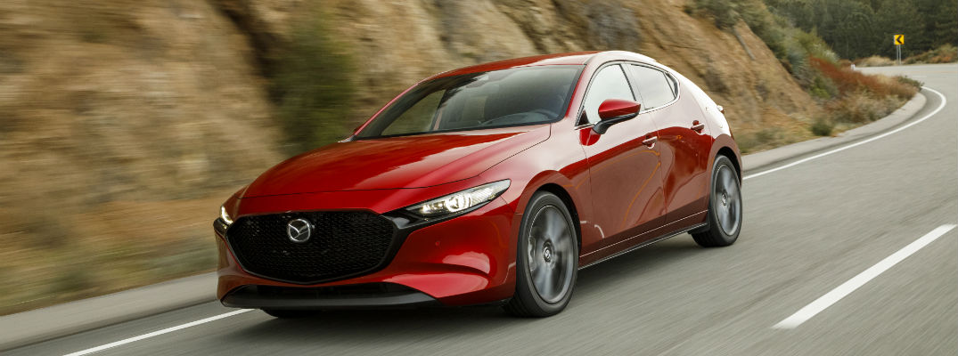 A front-right quarter photo of the 2019 Mazda3 Hatchback on the road.