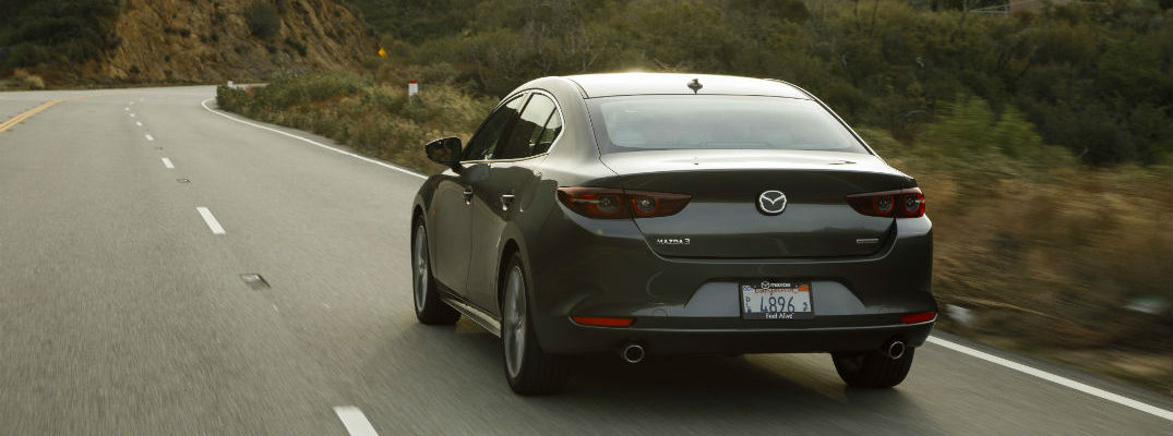 A rear photo of the 2019 Mazda3 sedan going down the road.